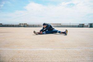 Man stretching on ground.