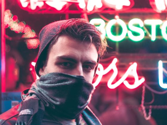 Guy wearing bandana in front of neon sign.