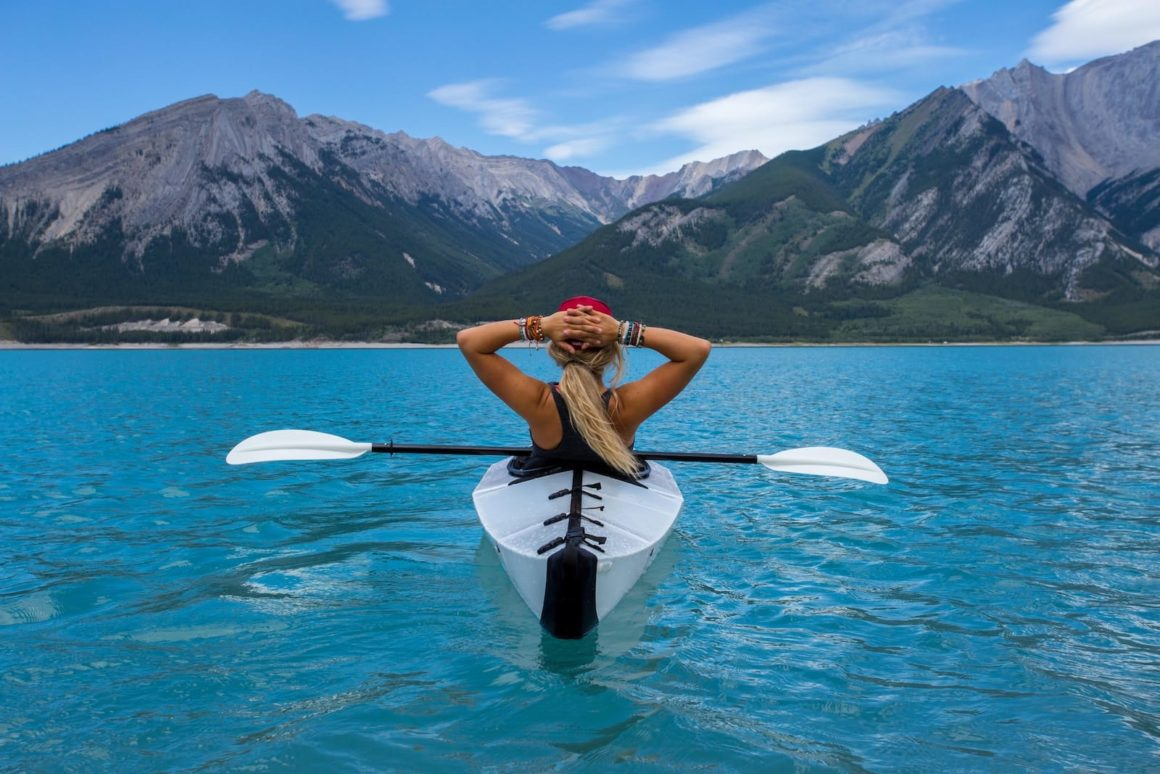 Woman on lake in canoe staring at mountains.