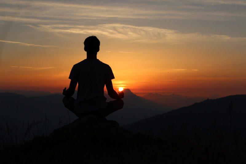 Man sitting at sunset meditating on hill.