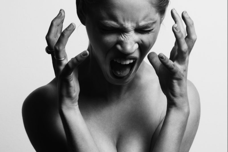 Woman screaming at herself in agony.