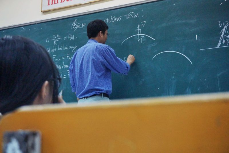 Teacher at chalkboard writing an equation that can't solve your suffering in life.