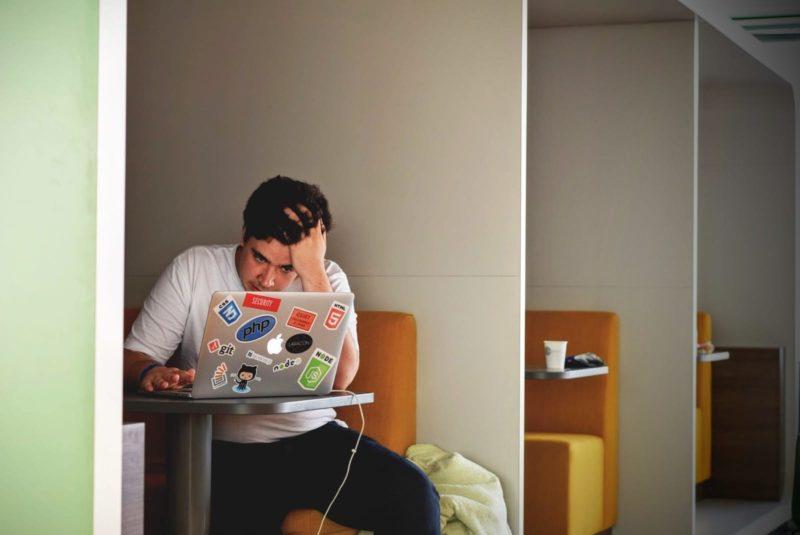 Frustrated freelancer at laptop.